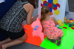 Parent and child with giant pattern blocks.